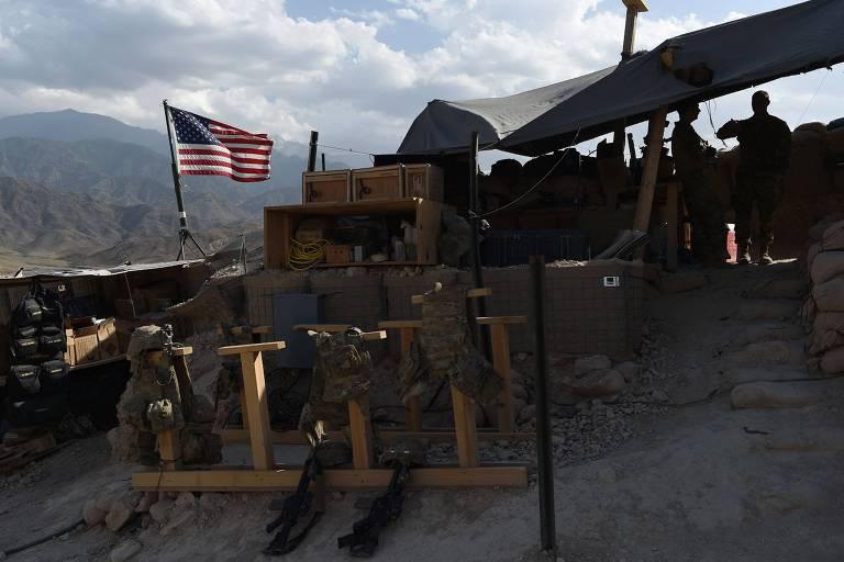Soldados americanos olham para bandeira dos Estados Unidos em local de patrulha