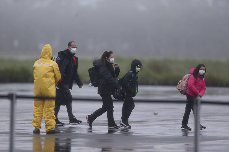 Pessoas andam na pista de pouso após desembarcarem de avião. Junto com eles está um agente que usa capa de chuva amarela.