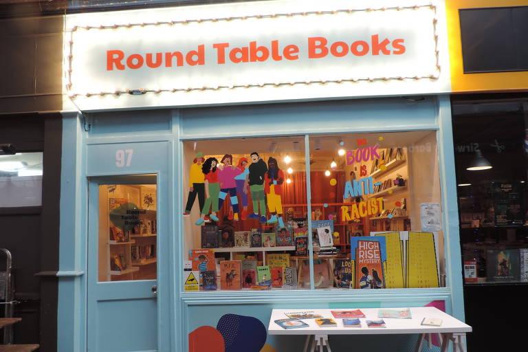 Vitrine de livraria vista da rua. Tem faixa branca com nome Round Table Books escrito em vermelho. Paredes da fachada azuis. Ambiente iluminado em tom amarelo dentro, com livros e outros artigos pendurados e organizados em prateleiras.