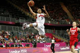Moore of the U.S. goes in for a lay-up past Canada's Murphy during the women's quarterfinal basketball match at the Basketball Arena in London