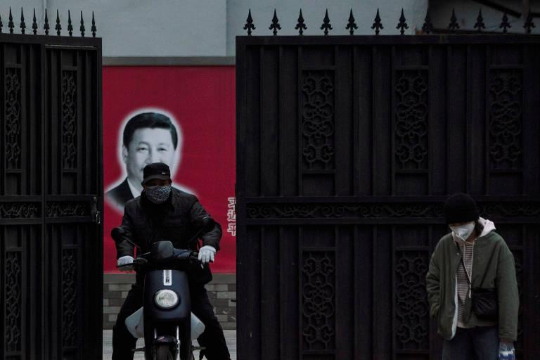 Com cartaz com o rosto de Xi Jinping ao fundo, moradores de Xangai usam máscaras para evitar a contaminação do coronavírus