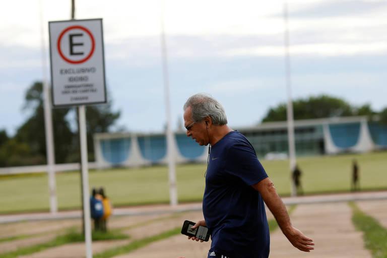 Paulo Guedes veste roupas de academia, segura um celular na mão e usa fones de ouvido; ao fundo está o Palácio da Alvorada