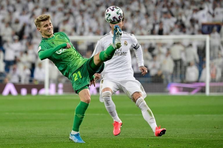 Jogador de verde controla a bola marcado pelo jogador de branco