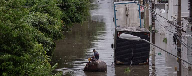 Em uma rua alagada, no lado direito da foto, estão dois caminhões submersos até a altura da cabine; do lado esquerdo há um canteiro de árvores medianas; no centro, um homem sentando em um grande tambor boia na enchente