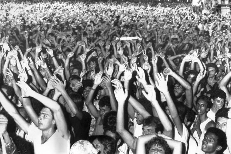 multidão de pessoas com as mãos para o alto  olhando para o palco