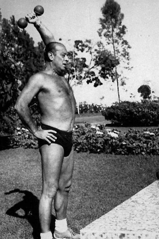 Figueiredo de sunga preta, tênis e meias está em um jardim. Ele levanta peso com sua mão direta enquanto a mão esquerda está em sua cintura