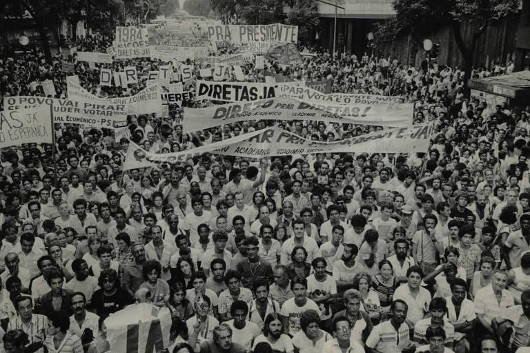 Multidão de pessoas de todos os tipos com cartazes a favor das eleições diretas