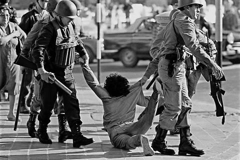 ORG XMIT: 214901_1.tif Policiais prendem operário durante protesto contra a ditadura militar organizado pela Confederação Geral de Trabalho em foto de 1982. (Archivo) Foto tomada el 30 de marzo de 1982, cuando guardias de infanteria de la Policia Federal detienen a un obrero en Av. 9 de Julio y Av. de Mayo en Buenos Aires durante una marcha contra la dictadura militar organizada por la Confederacion General del Trabajo (CGT). La Corte Suprema de Argentina declarú el 14 de junio de 2005 inconstitucionales las leyes de amnistóa que exculparon entre 1986 y 1987 a un millar de militares acusados de terrorismo de Estado durante la dictadura (1976-1983), informú el Alto Tribunal. La decisiún del más alto tribunal del paós le dará impulso a las causas aún abiertas por crómenes de lesa humanidad cometidas en las mazmorras dictatoriales, donde decenas de miles de opositores al régimen fueron torturados y unos 30.000 todavóa permanecen desaparecidos, según organismos de derechos humanos. AFP PHOTO / Daniel GARCIA