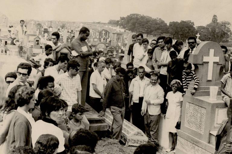 Pessoas em torno de um caixão sendo enterrado no cemitério