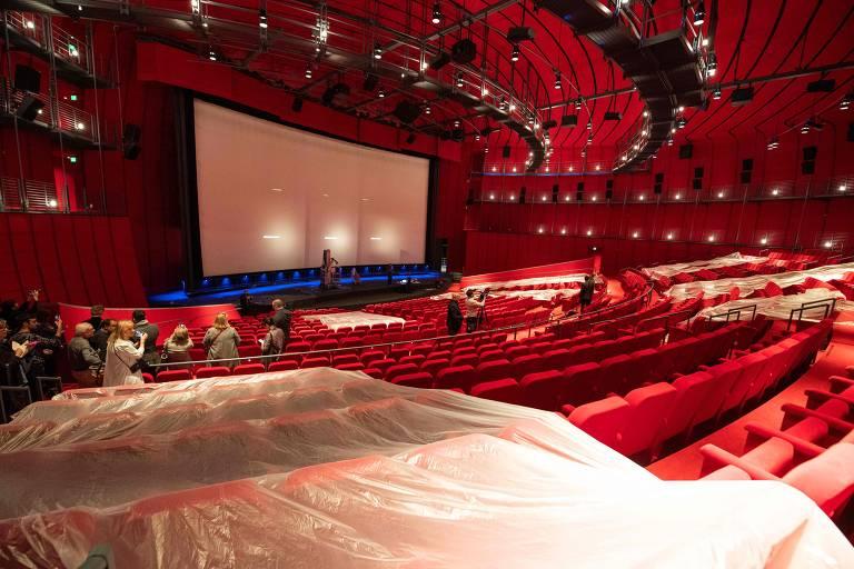 Sala de cinema com poltronas e teto em tecido vermelho