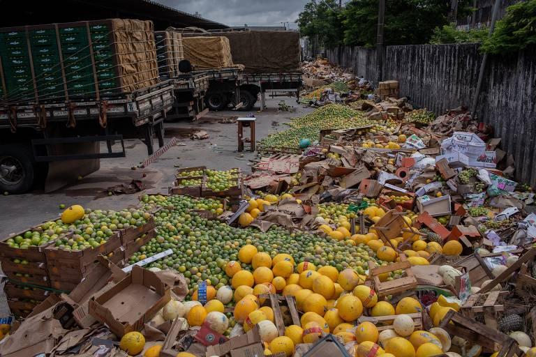 Laranjas e outras frutas jogadas pelo chão da Ceagesp