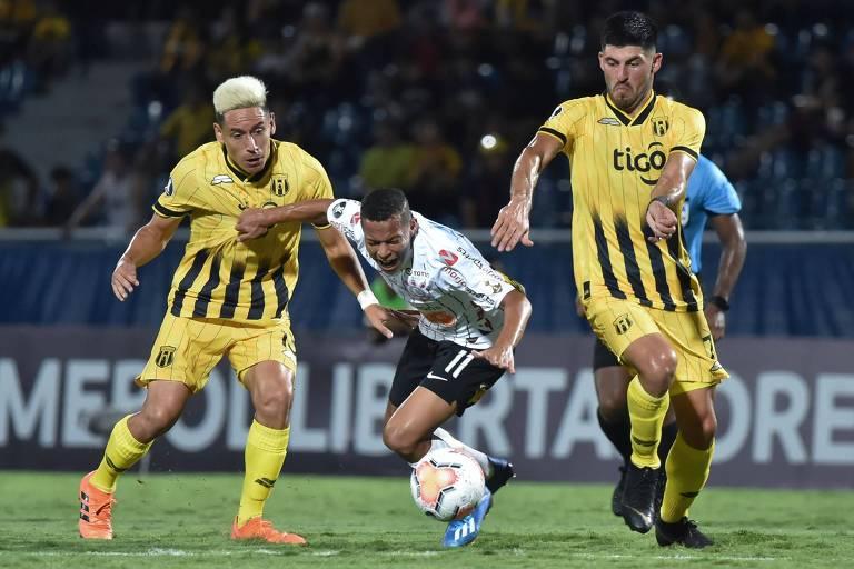 O corintiano Janderson (centro) é derrubado durante disputa de bola com os jogadores do Guaraní, rival do Corinthians na disputa da pré-Libertadores 2020