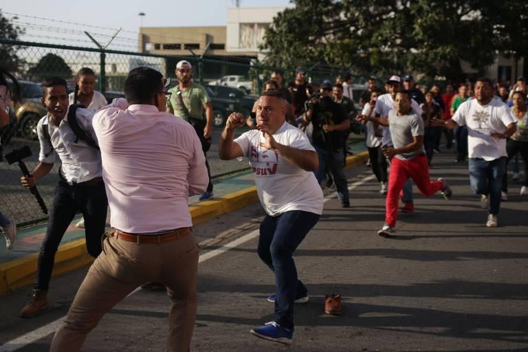 Apoiador de Maduro, ao centro, confronta um jornalista enquanto o líder opositor venezuelano Juan Gauidó desembarca no aeroporto internacional Simon Bolívar