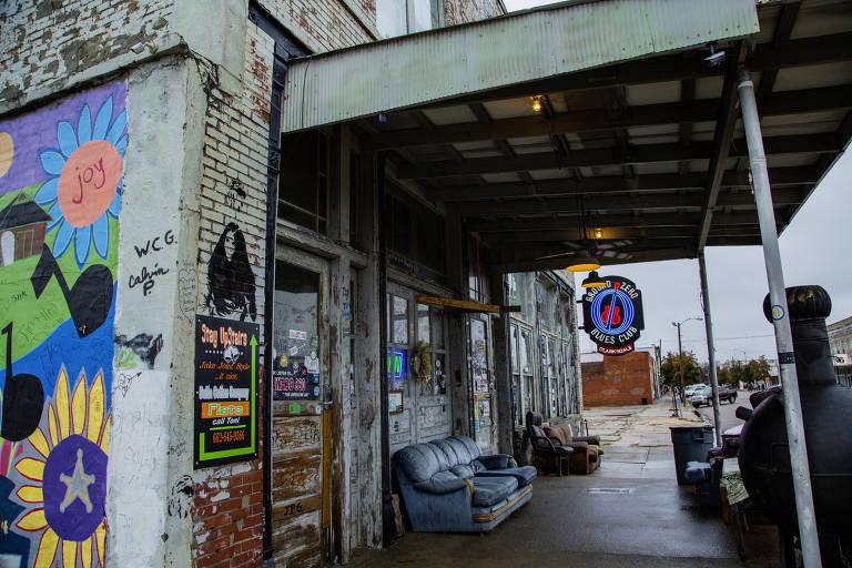 """Entrada de clube de blues com paredes grafitadas e pixadas, dois sofás velhos e uma cadeira de escritório encostados e um luminoso onde se lê """"Ground Zero Blues Club"""