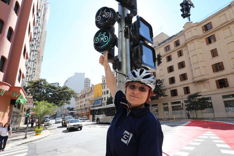 Renata Falzoni aponta para um semáforo da ciclovia