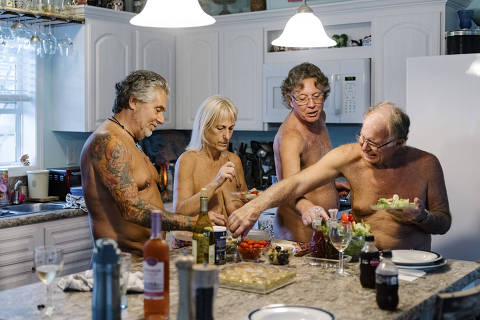 A dinner party at Jack Clark's house in the Lake Como Family Nudist Resort in Lutz, Fla., Jan. 11, 2020. From left: Jayson and Karyn McMullen, Clark and Charle Herndon. Despite the occasional splatter burn, nudists say their relationship to eating, at home or in restaurants, is better and healthier without all the clothing. (Jason Henry/The New York Times) ORG XMIT: XNYT118