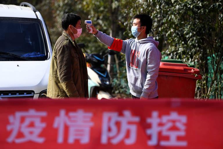 Voluntário mede a temperatura de morador de cidade no leste da China por causa do coronavírus