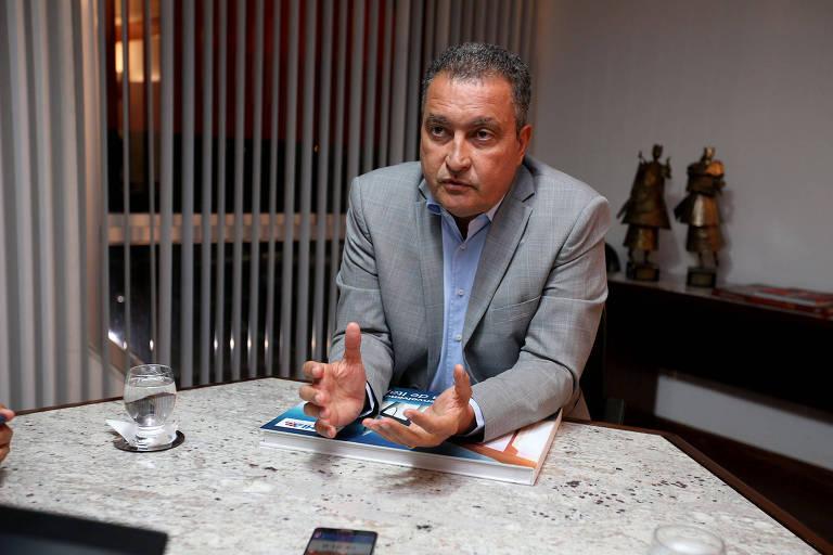O governador da Bahia, Rui Costa, sentado em mesa