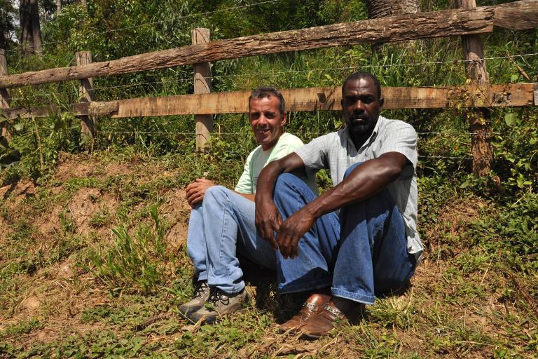 dois homens sentados em frente a uma cerca