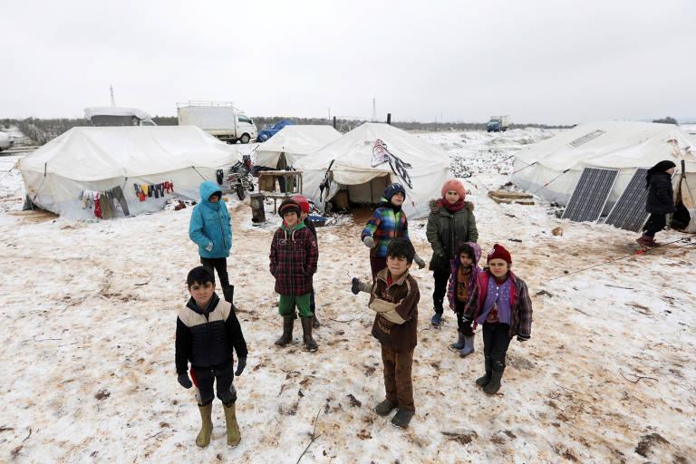Crianças vestindo casacos de inverno estão de pé em campo com neve; atrás, barracas precárias também cobertas de neve