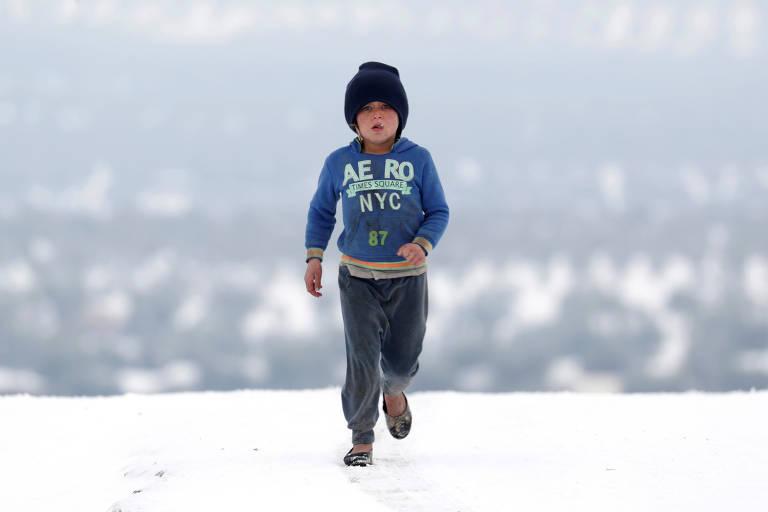 Menina caminha em acampamento para deslocados internos em Azaz coberto de neve