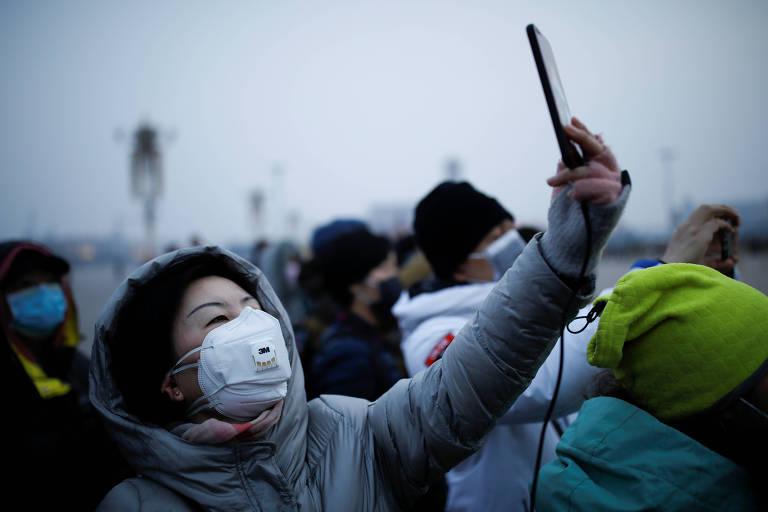 Mulher usa celular na praça Tiananmen em Pequim, na China