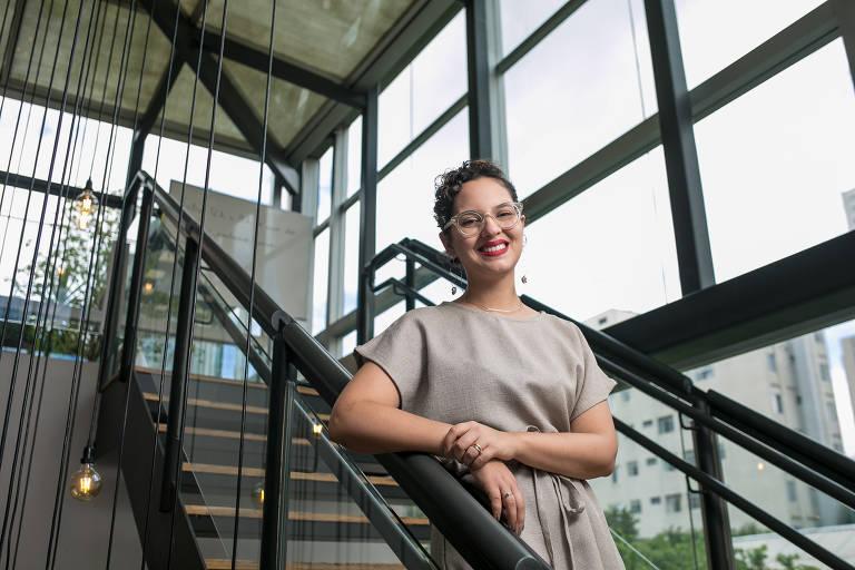 Mulher sorri para a foto apoiada com o braço direito em um corrimão de uma escada