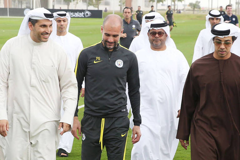 O técnico Pep Guardiola (ao centro) e o xeque Mansour bin Zayed (de marrom), proprietário do City Football Group