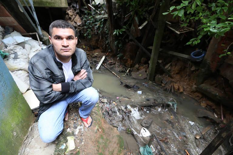 O vigilante Juscelino Gomes Maciel, 36 anos, mostra a situação em seu bairro; pai de três meninas, ele teme pela saúde das crianças, que acabam se expondo ao lixo e aos insetos em viela de Paraisópolis