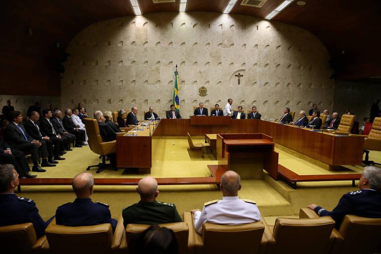 Vista do plenário do STF, chão amarelo, ao centro bancadas com os ministros  e ao redor convidados sentados em suas cadeiras