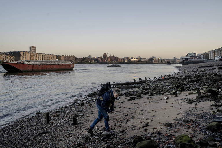 Lara Maiklem looks for items from London's past along the Thames River on Nov. 29, 2019. From ribald tokens from London?s Roman past to hints of the Mayflower?s fate, mudlarks discover the story of a constantly changing London ? but only at low tide. (Andrew Testa/The New York Times)