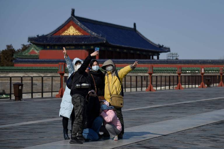 Quatro adultos e uma criança trajando máscaras posam para selfie frente a construção histórica chinesa