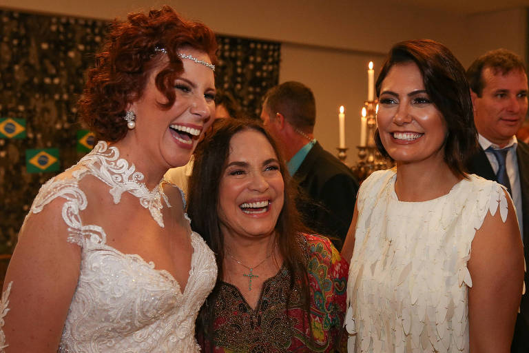 Carla Zambelli sorri abraçada com Regina Duarte enquanto Michelle Bolsonaro sorri olhando para o outro lado