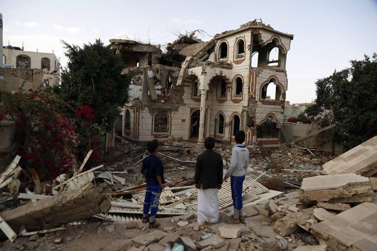 Crianças observam escombros de um prédio destruído