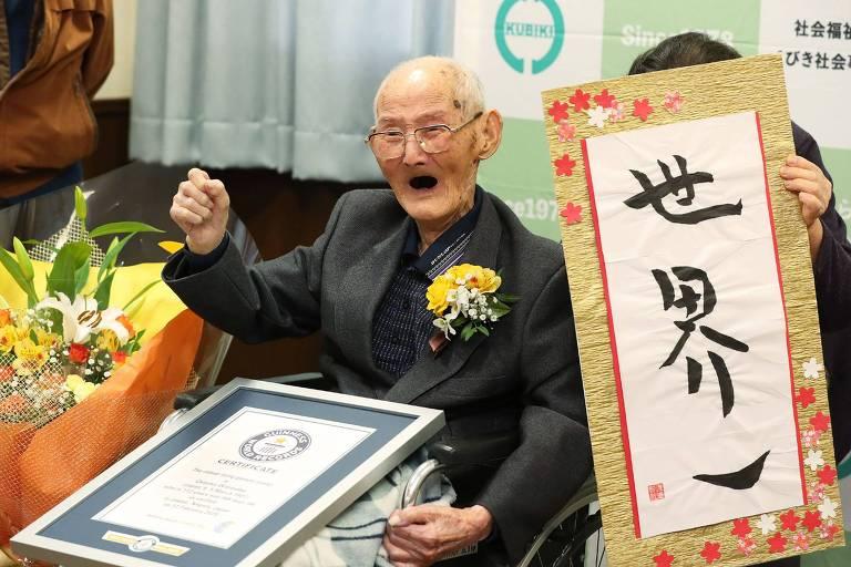"""Chitetsu Watanabe, 112, posa ao lado de caligrafia japonesa em que se lê """"Número 1 do Mundo"""" depois de receber o prêmio de homem mais velho do mundo"""