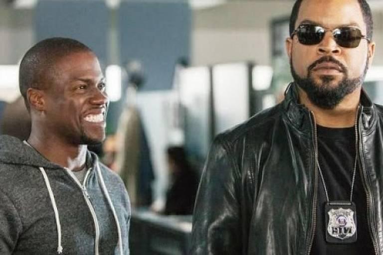 Dois homens negros estão na imagem. Um deles é policial com distintivo pendurado no pescoço e jaqueta jeans e o outro está sorrindo com blusa moletom