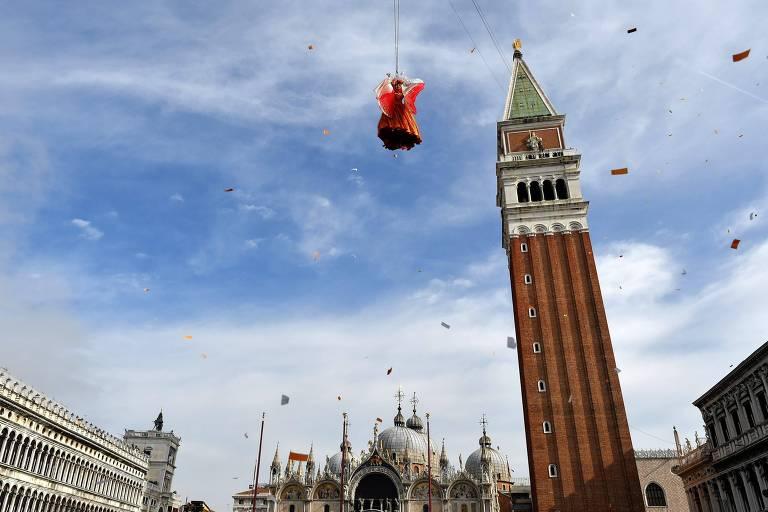 """Mulher com roupa vermelha espalhafatosa """"voa"""" içada por cabos, olhada do chão. Basílica de São Marcos aparece no fundo"""