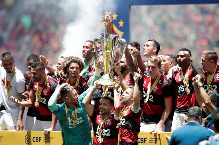 Jogadores do Flamengo levantam a taça após a vitória sobre o Athletico-PR neste domingo (16), pela Supercopa do Brasil, em Brasília