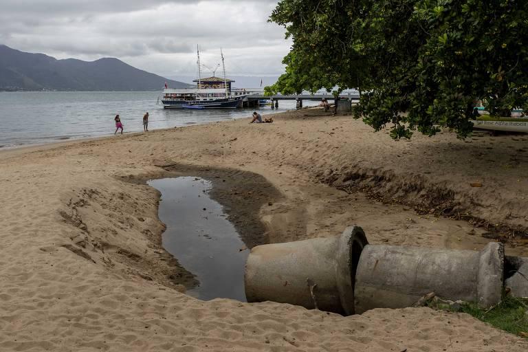 Cano despeja água na praia, que moradores dizem estar poluída