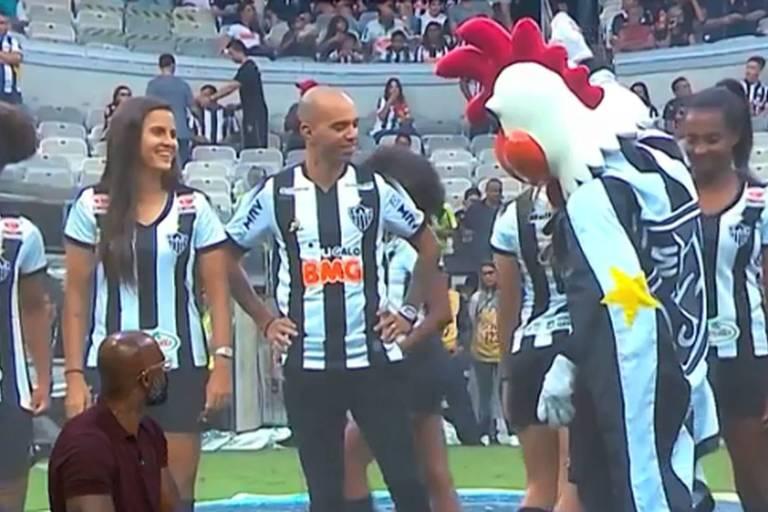 Mascote do Atlético-MG pede para jogadora  Vitória Calhau  exibir o corpo durante apresentação do time feminino junto com o atacante Diego Tardelli
