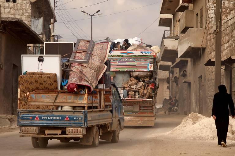 Sírios fugindo dos combates passam pela cidade de Darret Ezza, noroeste de Alepo