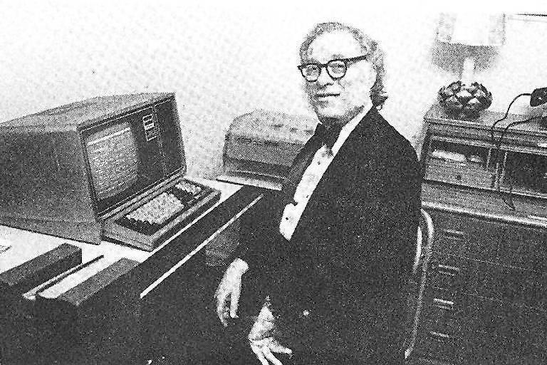 Em foto antiga, preto e branco, Asimov está sentado em frente a um computador, com o dorso e a cabeça virados em direção à câmera. Ele usa óculos e veste um smoking.