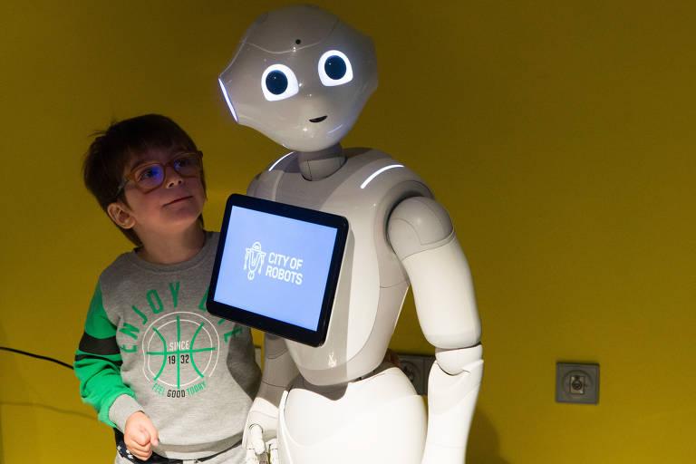 Criança está ao lado de robô humanoide