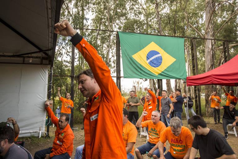 Em primeiro plano, um homem veste um macacão laranja e ergue o braço; ao fundo da foto estão outros trabalhadores trajando a mesma roupa