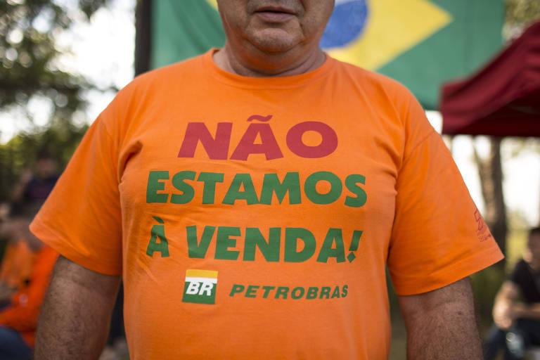 """Retrato focado na camisa de um homem; ela é laranja e tem escrito """"não estamos à venda"""" com o logo da petrobras embaixo"""