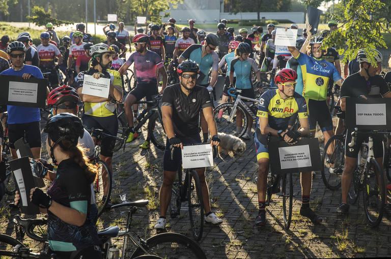 Grupo está parado sobre biciclistas e segurando cartazes