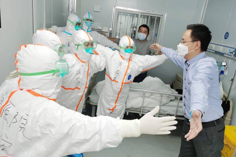 """O Sr. Wang, 36, um paciente recuperado de coronavírus, """"abraça"""" a equipe médica sem contato corporal antes de deixar o Hospital Leishenshan (Thunder God Mountain) em Wuhan, capital de na província de Hubei, no centro da China, em 18 de fevereiro de 2020. O Hospital Leishenshan, um hospital improvisado construído em Wuhan em meio à nova doença por coronavírus (COVID-19) teve os dois primeiros pacientes curados nesta terça-feira (18), incluindo Wang e uma paciente de 83 anos"""