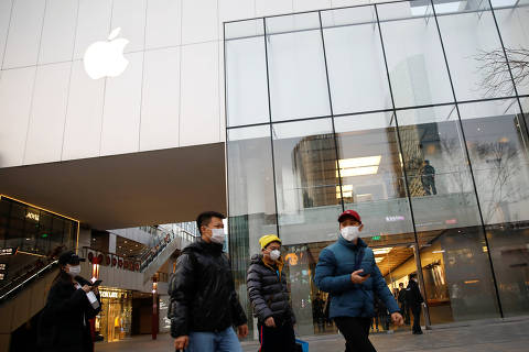 People wearing face masks walk in front of an Apple store at a shopping mall, as the country is hit by an outbreak of the new coronavirus, in Beijing, China February 18, 2020. REUTERS/Carlos Garcia Rawlins ORG XMIT: CH102