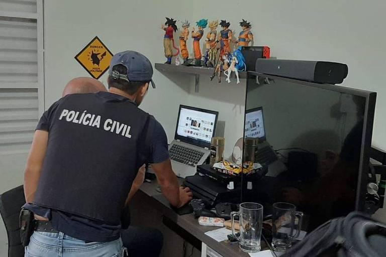 Homem de camiseta preta e boné olhando computadores em escrivaninha
