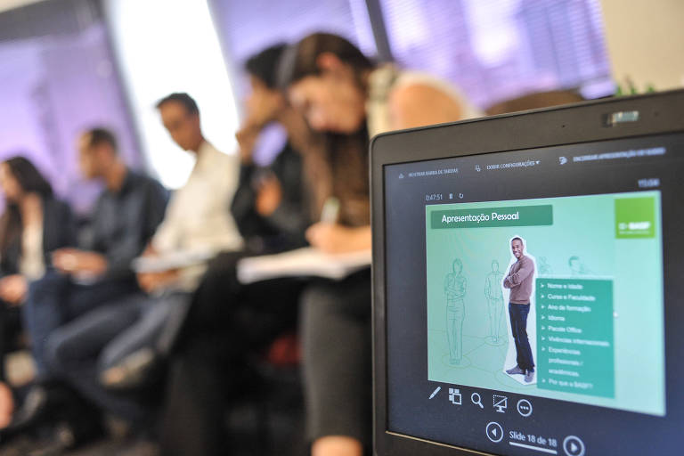Candidatos a uma vaga de estágio aparecem sentados ao fundo. Em primeiro plano, uma tela de computador mostra um slide sobre apresentação pessoal